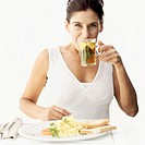 Woman drinking herbal tea and eating scrambled eggs and toast