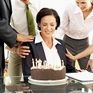 Businesswoman sitting in front of a birthday cake with candles lighting
