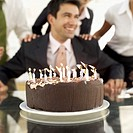 Businessman sitting in front of a birthday cake in an office