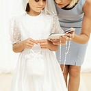 Young woman giving a rosary bead and prayer book to a girl (11-13) wearing her first holy communion dress
