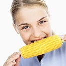Portrait of a young woman eating corn on the cob