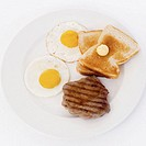 Elevated view of fried eggs served with toast and steak