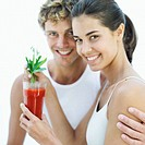 Young couple holding a glass of tomato juice with a celery stick
