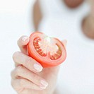 Close-up of half a tomato in a young woman´s hand