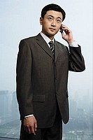 Businessman looking away, using mobile phone