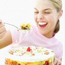 Teenage girl (16-18) lifting a spoonful of fruit trifle from a bowl (blurred)