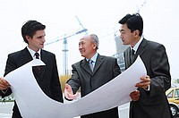 Businessmen standing and looking at blue print, cranes in the background