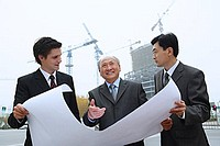 Businessmen with blue print, cranes in the background