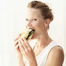Portrait of a young woman biting into a burger