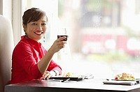 Woman sitting at table, raising drink towards camera, smiling
