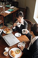 Two businesswomen at cafe, drinking coffee, laptop on table