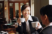 Two businesswomen at cafe, holding cups, smiling