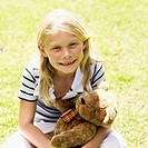 Portrait of young girl (10-11) sitting holding her teddy bear