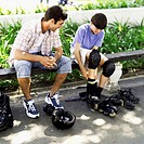 boy (12-13) sitting outdoors with his father putting on his roller skates