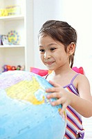 Young girl smiling and looking at globe