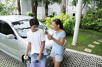 Couple next to car, man with soap suds on face, woman next to him, laughing