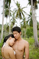 Woman resting head on mans shoulder, coconut trees in the background