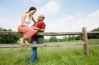Woman sitting on wooden fence, boyfriend standing (thumbnail)