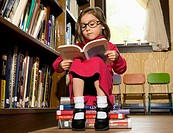 Young girl reading in a library (thumbnail)