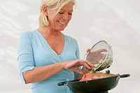 ELDERLY PERSON IN  KITCHEN<BR>Model.<BR>Cooking with a wok.