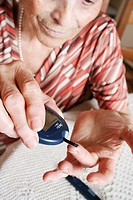 TEST FOR DIABETES<BR> <BR>Elderly woman affected by diabetes type 1 is testing her glycemia with a glucometer.