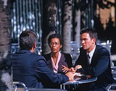 businesswoman in a meeting with two men at an outdoor cafe