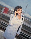 businesswoman talking on a mobile phone at a station platform