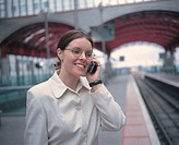 close-up of a woman talking on a mobile phone at a station platform