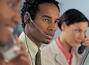 man wearing telephone headset sitting in office with his coworkers