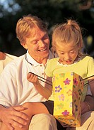 young girl (6-8) peeping in bag while sitting on fathers lap