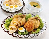 high angle view of two small roast chickens garnished with boiled egg and served with condiments
