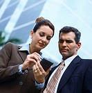 low angle view of a young businessman and business woman using a hand held device