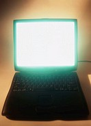close-up view of a laptop with the screen glowing
