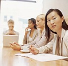 four businesswomen sitting in a conference room