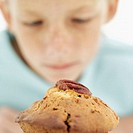 Young girl (10-11) staring at a muffin