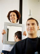 hairdresser holding a mirror behind a young man