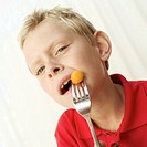 Young boy (8-9) eating a carrot with a fork