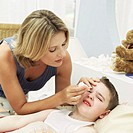 Young woman putting eye drops in sons eyes