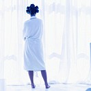 Young woman standing near window in bathrobe