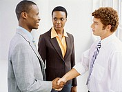 businesswoman looking at two businessmen shaking hands