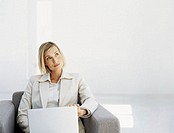 businesswoman sitting in front of a laptop and thinking