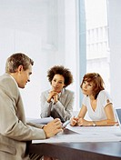 businessman and two businesswomen sitting in a boardroom