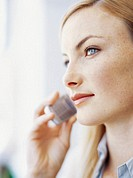 side view of businesswoman listening on a mobile phone in an office