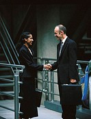 Young businessman and a young businesswoman shaking hands