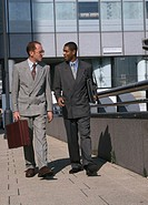Two young business executives walking together
