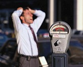 Young businessman standing behind an expired parking meter with his hands on his head
