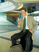 businessman holding a mobile phone at an airport