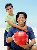 portrait of a father holding a beach ball with his son hugging him