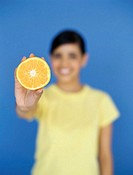 portrait of a young woman holding a cut orange