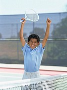 portrait of a boy holding a tennis racket and raising his arms